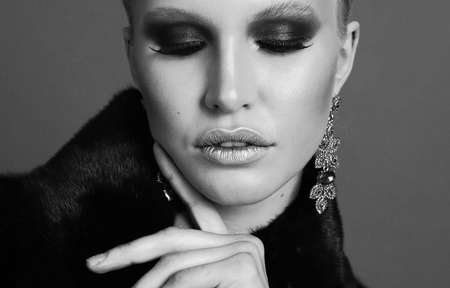 fashion photo of glamour beautiful woman with blond hair and smokey eyes makeup,wears luxurious fur coat, bijou and headband Archivio Fotografico