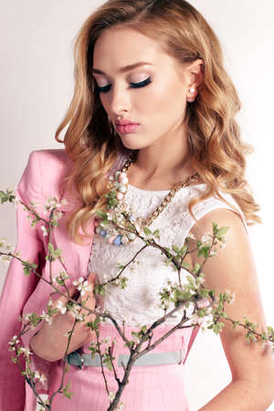 fashion studio photo of beautiful young woman with blond curly hair, wears elegant clothes and bijou, posing on the spring background