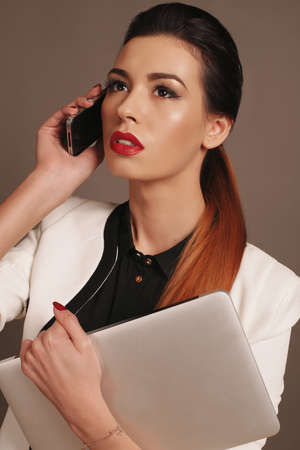 businesslike: fashion photo of beautiful elegant businesslike lady speaking by mobile Stock Photo