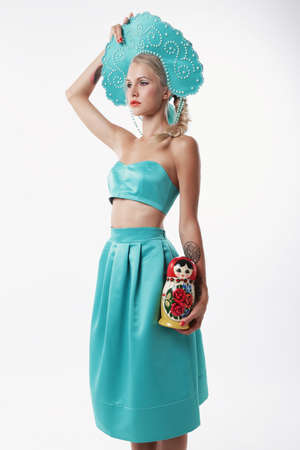 russian hat: fashion studio photo of gorgeous woman with blond hair in russian national hat holding matrioshka doll