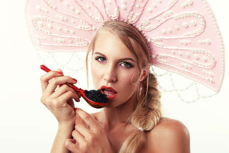 russian hat: fashion studio photo of gorgeous woman with blond hair in russian national hat, eating red caviar Stock Photo
