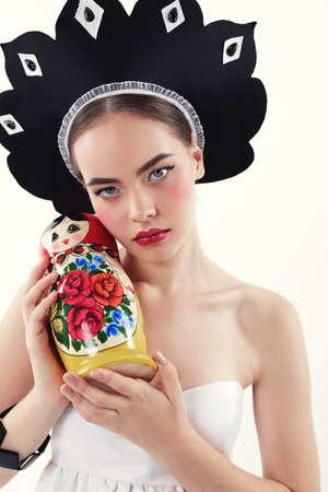 matrioshka: fashion studio photo of gorgeous woman with blond hair in russian national hat holding matrioshka doll