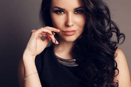 fashion studio photo of gorgeous woman with dark hair and evening makeup in elegant dress Stock Photo