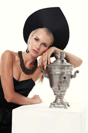 fashion studio photo of gorgeous woman with blond hair in russian national hat with samovar