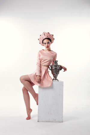 russian hat: fashion studio photo of gorgeous woman with brunette hair in russian national hat with samovar