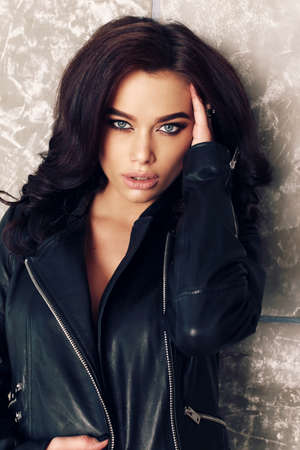 fashion interior photo of gorgeous woman with long dark hair in leather jacket Stock Photo