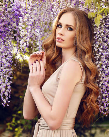 luxurious: fashion outdoor photo of gorgeous woman with luxurious hair in elegant dress, posing in blossom spring garden
