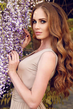 glamour hair: fashion outdoor photo of gorgeous woman with luxurious hair in elegant dress, posing in blossom spring garden