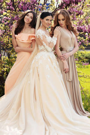 fashion outdoor photo of gorgeous bride in luxurious wedding dress posing with beautiful bridesmaids