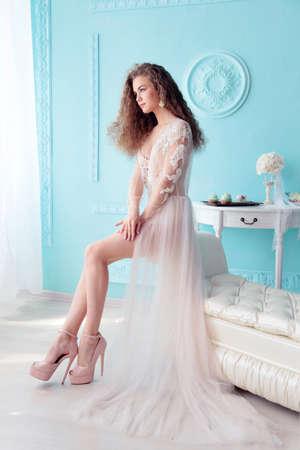studio fotografico di moda di bella giovane sposa con i capelli ricci scuri in abito da sposa di lusso che propone alla stanza