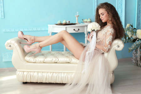 luxurious: fashion studio photo of beautiful young bride with dark curly hair in luxurious wedding dress posing at room