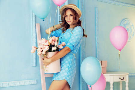 fashion interior photo of beautiful young girl with dark curly hair and tender makeup, posing with colorful air balloons Foto de archivo