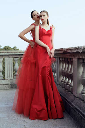 fashion outdoor photo of gorgeous young women with dark hair in elegant red  dresses posing beside old castle Stock Photo