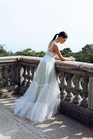 fashion outdoor photo of gorgeous young bride with dark hair in elegant wedding dress posing beside old castle