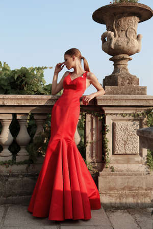 fashion outdoor photo of gorgeous young woman with dark hair in elegant red  dress posing beside old castle