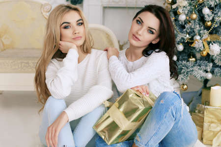 fashion interior holiday Christmas photo of beautiful women in cozy home clothes celebrating New Year holidays