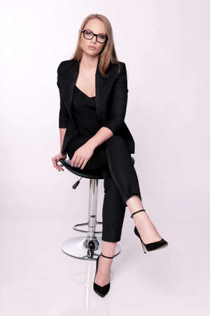 businesslike: fashion studio photo of businesslike woman with blond straight hair in elegant office outfit and glasses