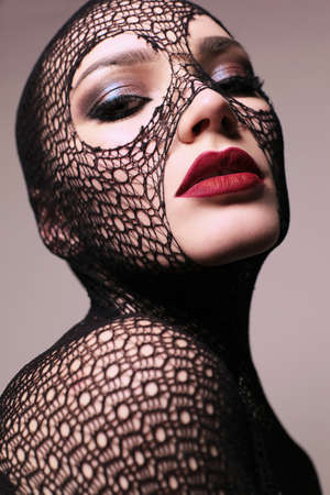 fashion studio portrait of gorgeous sensual woman with dark hair with transparent veil on face