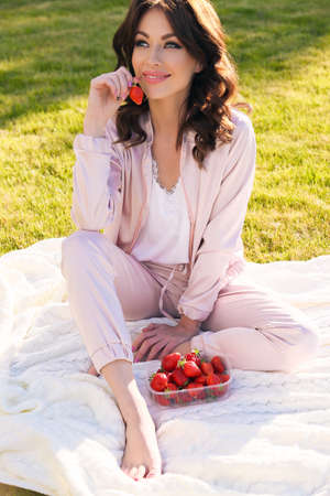 fashion outdoor photo of beautiful girl with dark hair in elegant dress relaxing at summer picknic, eating strawberries Stock Photo