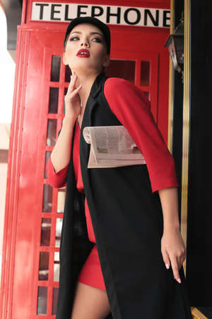 fashion outfoor photo of gorgeous sexy girl with dark hair walking by the street,decorated as London style, red phone booth on background Foto de archivo