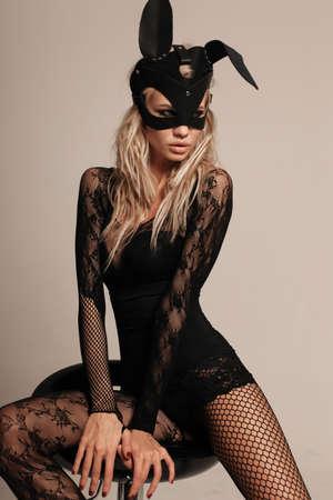 顔にバニーマスクとセクシーな服を着たブロンドの髪を持つセクシーな女性のファッション写真