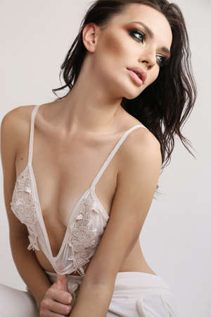 fashion studio photo of beautiful woman with dark hair and evening makeup in elegant lingerie