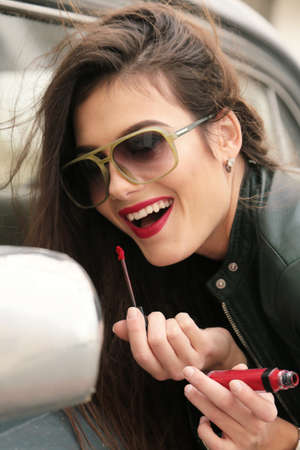 fashion outdoor photo of beautiful girl with dark hair in casual clothes posing near auto, wearing lipstick Foto de archivo