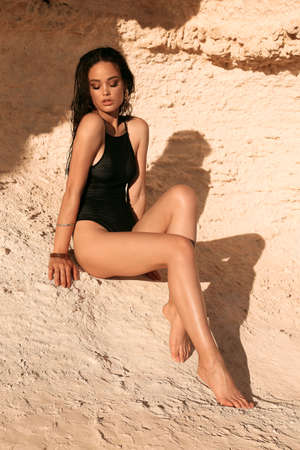 fashion outdoor photo of beautiful sexy woman with dark hair in elegant black swimming suit relaxing on summer beach near rock