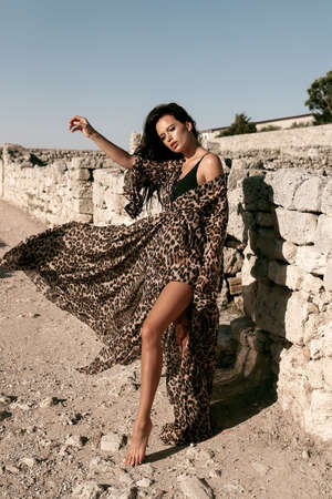 fashion outdoor photo of beautiful sexy woman with dark hair in elegant swimming suit and tunic posing among stones in antic place