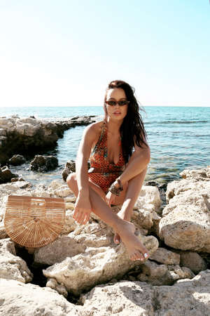 fashion outdoor photo of beautiful sexy woman with dark hair in elegant swimming suit relaxing on summer beach
