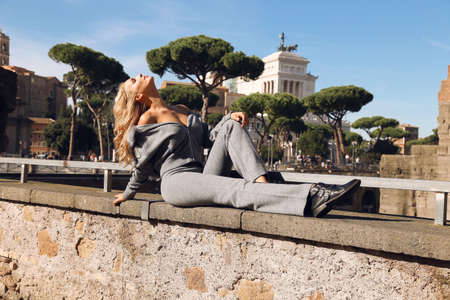 fashion outdoor photo of beautiful sexy woman with blond hair in cozy casual suit posing in antic italian city Stock Photo