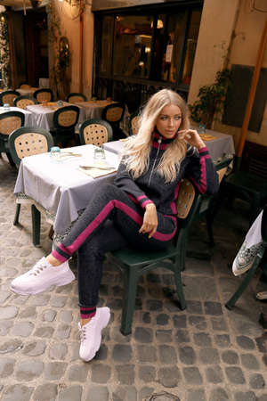 fashion outdoor photo of beautiful woman with blond hair in casual cozy clothes sitting in italian outdoor restaurant Stock Photo