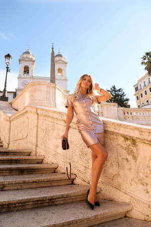 fashion outdoor photo of beautiful girl with long blond hair in elegant dress posing in Rome street Banco de Imagens - 117035106
