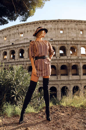 fashion outdoor photo of beautiful woman with blond hair in elegant clothes and hat posing near Colosseum in Rome Banco de Imagens - 117605130