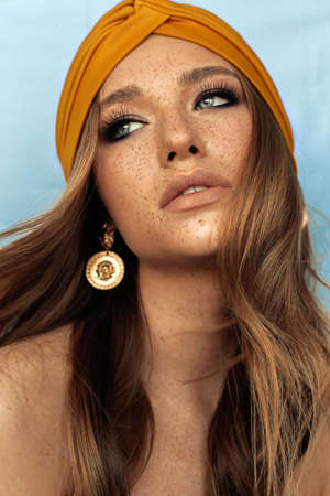 fashion studio portrait of beautiful young woman with brown hair and freckles face