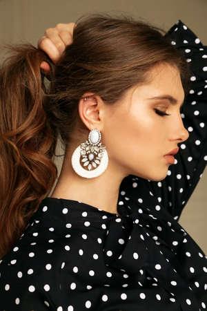 Modestudiofoto einer schönen Frau mit dunklen Haaren in eleganter Bluse
