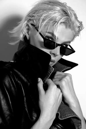fashion photo of beautiful woman with short blond hair in elegant clothes with sunglasses posing in studio