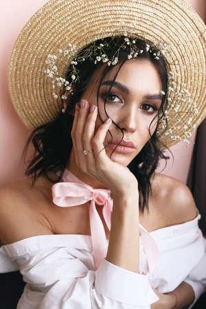 foto in studio di moda di una bellissima giovane donna con i capelli scuri con un tenero trucco naturale, in abiti eleganti e cappello di paglia con fiori decorativi