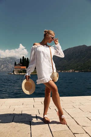 fashion outdoor photo of beautiful sensual woman with blond hair in elegant dress and straw hat and bag, posing in Montenegos city Perast Stock Photo