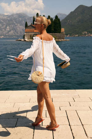 fashion outdoor photo of beautiful sensual woman with blond hair in elegant dress and straw hat and bag, posing in Montenegos city Perast Stok Fotoğraf