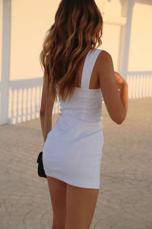 fashion  photo of beautiful sensual woman with blond hair in elegant dress and accessories posing on the summer beach