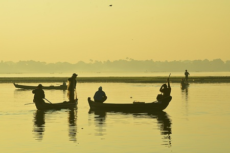 lao: Silhouette of fishermen with sunrise sky in the background  Stock Photo