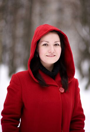 Smiling pretty girl with hood in the red coat Stock Photo - 9371881