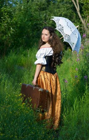 Young beautiful woman in vintage dress with old suitcase photo