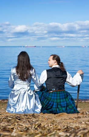 broadsword: Woman and man in scottish costume with sword sitting near the sea