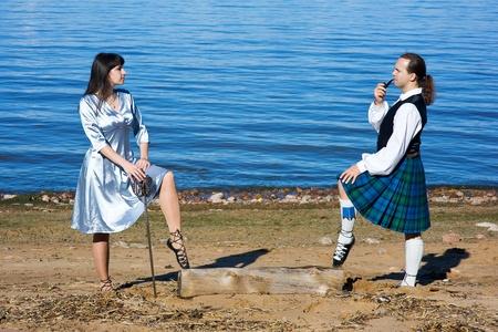 highlander: Mujer con la espada y el hombre en traje de escocés con el tubo, cerca del mar Foto de archivo