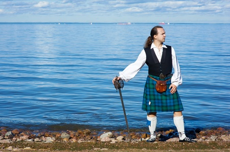 scot: Man in scottish costume with sword looking at the sea Stock Photo
