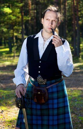 highlander: El hombre en traje de escocés con la espada y la tubería Foto de archivo