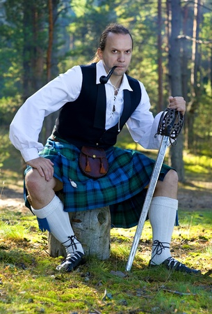 Handsome man in scottish costume with sword and pipe outdoor Stock Photo