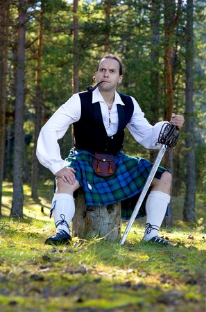 scot: Handsome man in scottish costume with sword and pipe outdoor Stock Photo